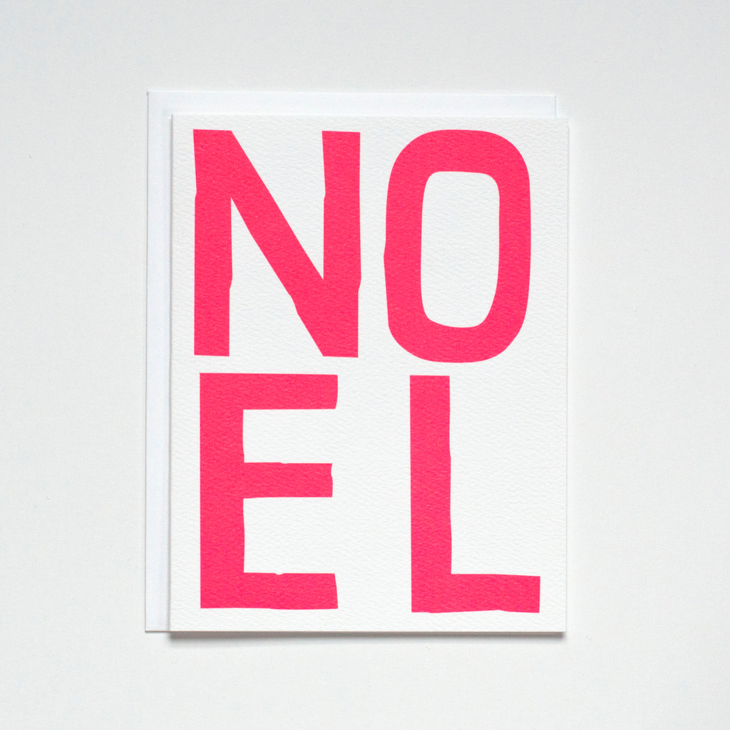 aNotecard reads NOEL in a bold neon red hand drawn type