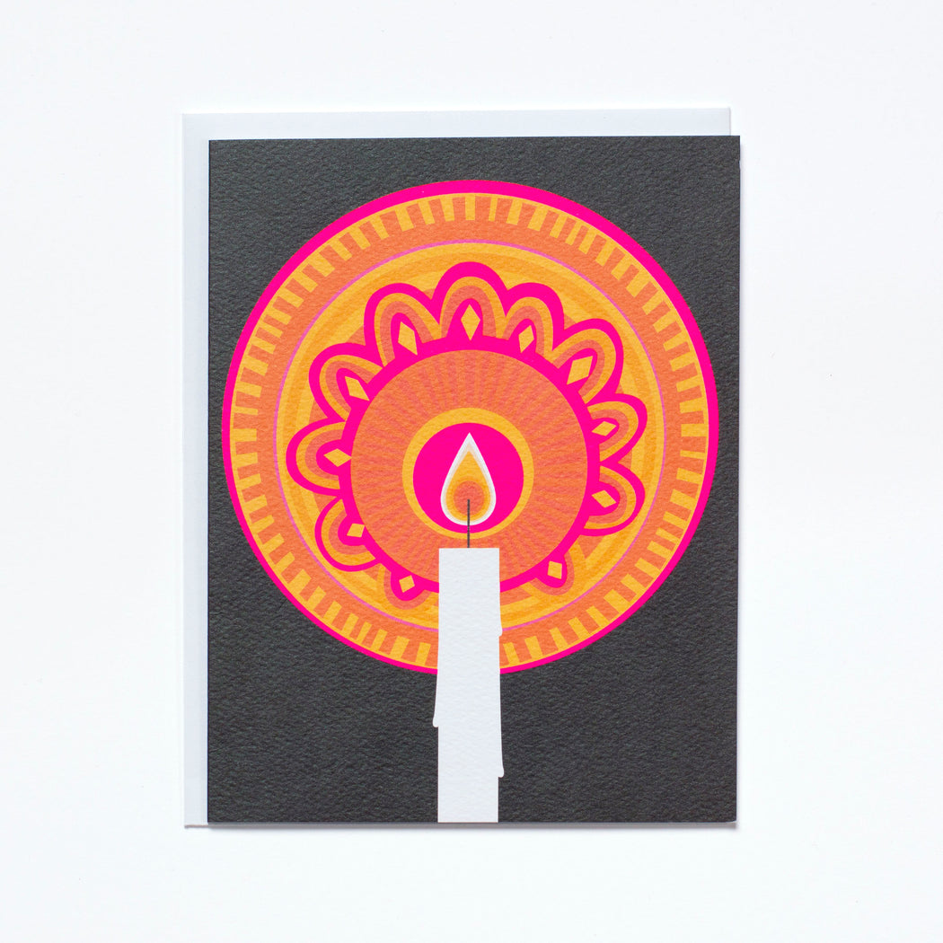 lit candle with pink and orange pattern on a black background