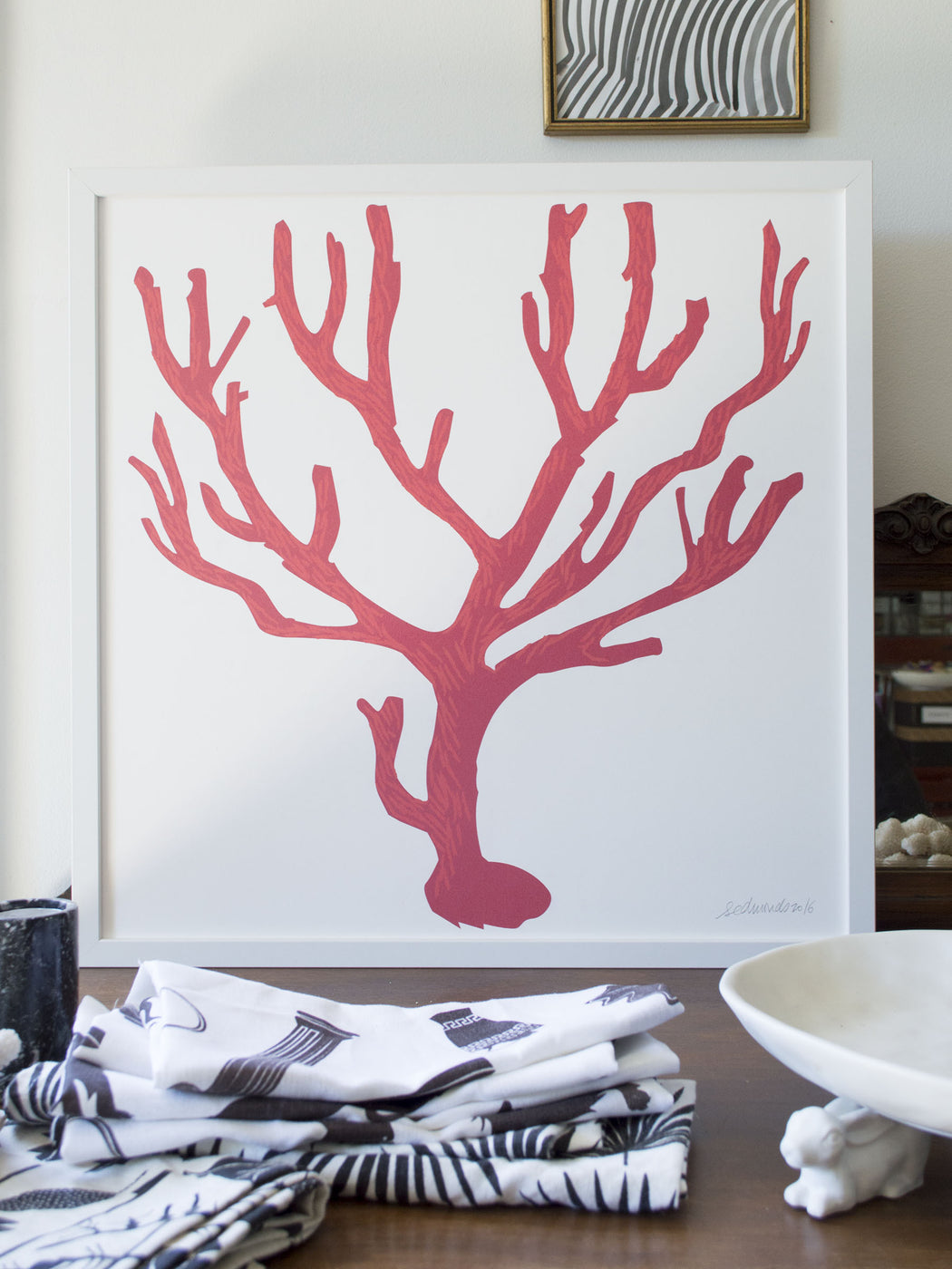 Banquet's framed Italian red coral screenprint with folded table linens.
