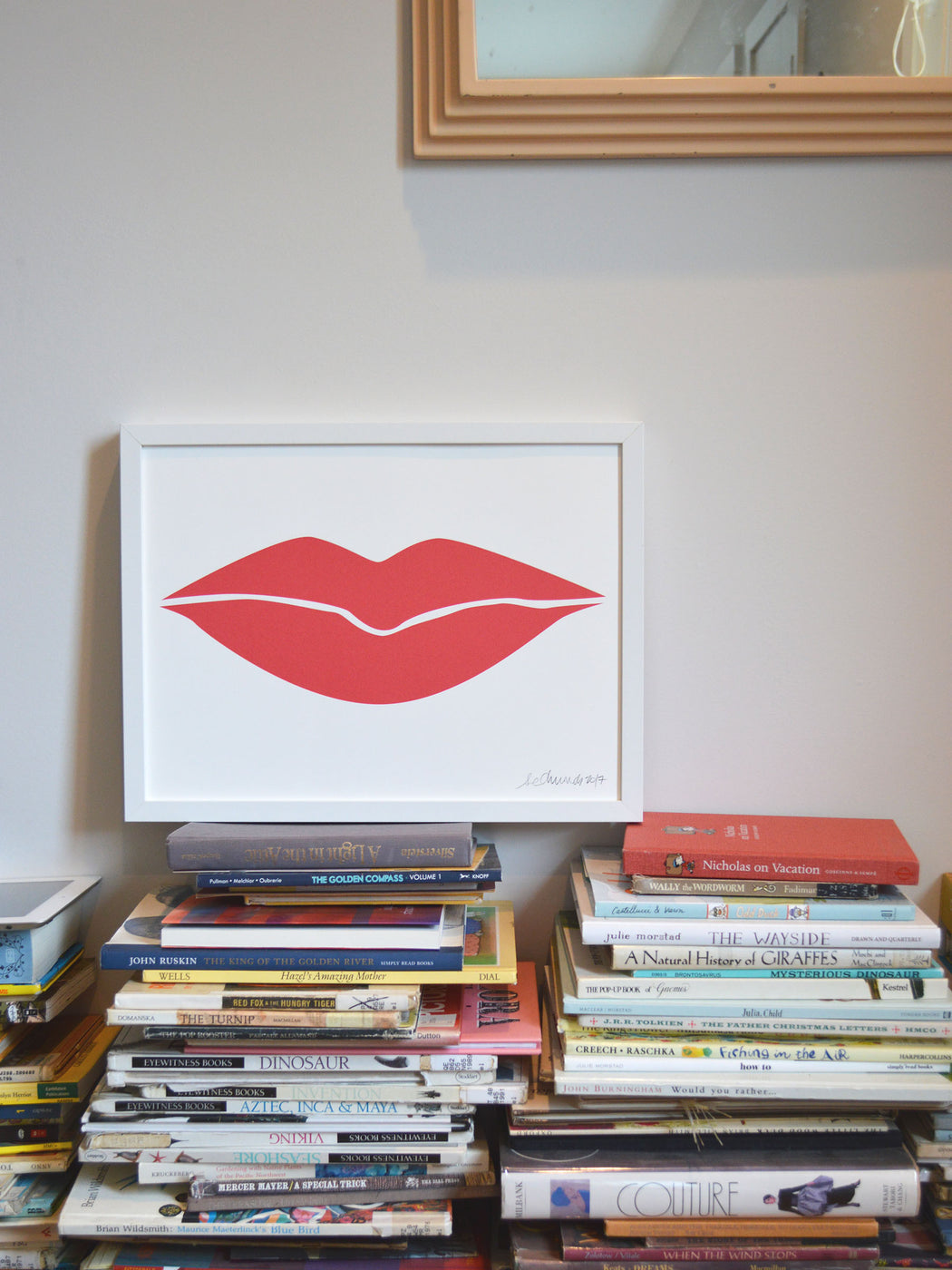 Banquet Workshop's lip print sitting on a stack of books in a home