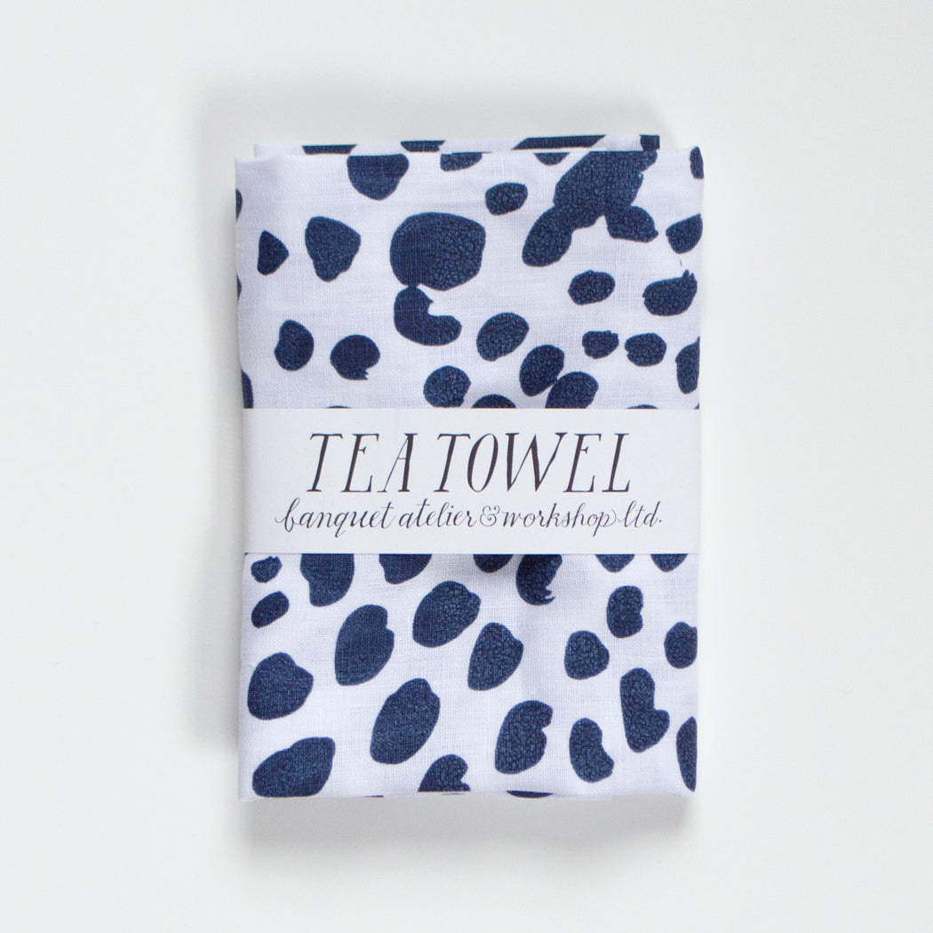 Animal spots in navy on a white, screen printed tea towel from Banquet Workshop