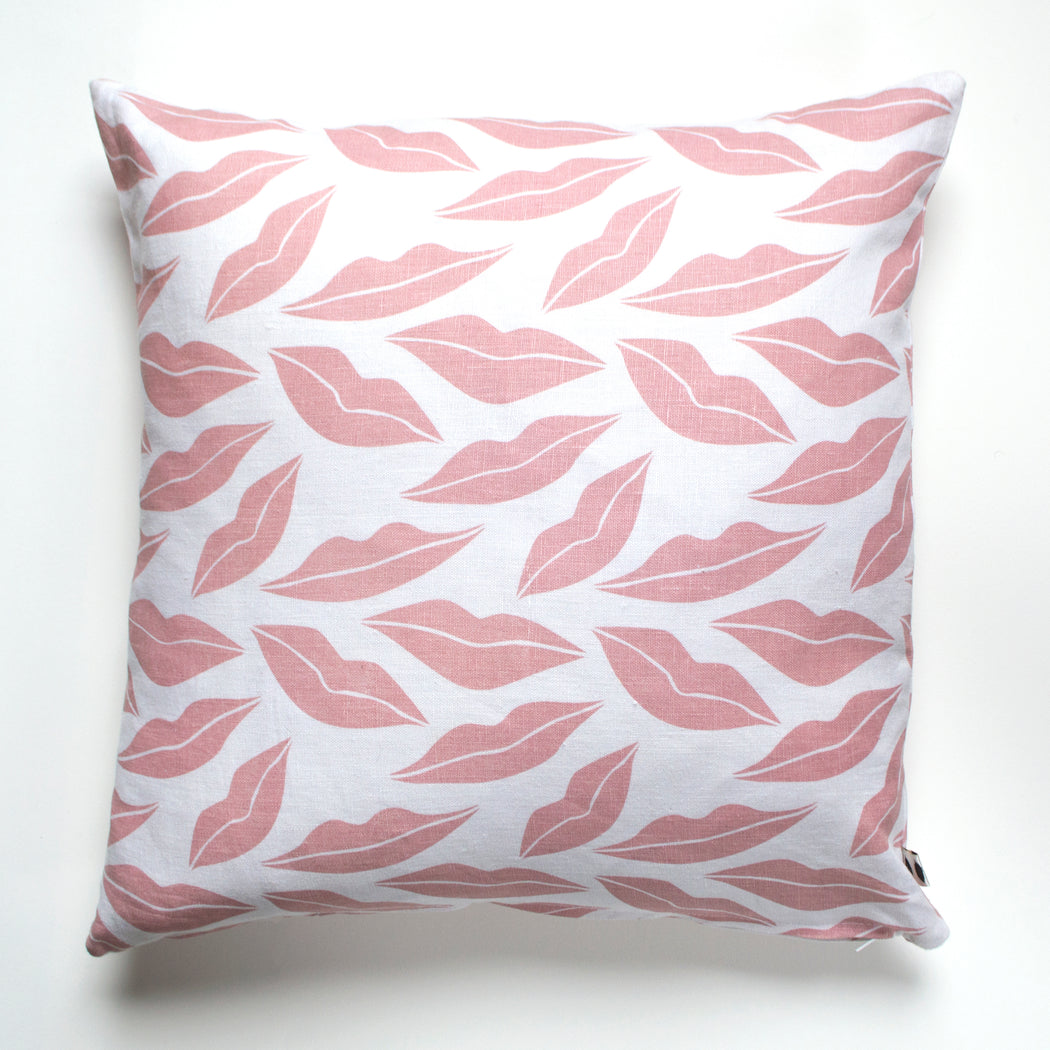 Blush pink lips scattered across a white 100% linen pillow.