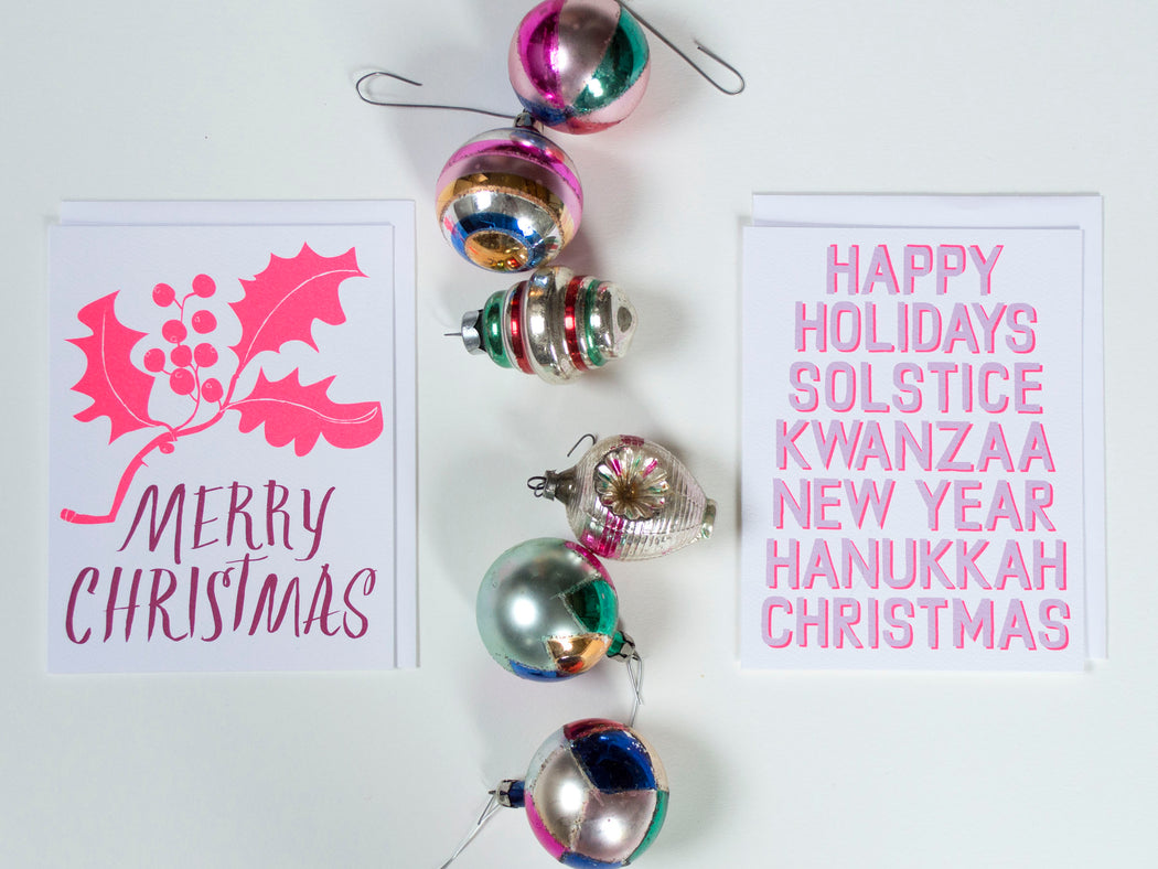 Styled shot of Banquet Workshop note cards with graphic text reading Happy Holidays Solstice Kwanzaa New Year Hanukkah Christmas