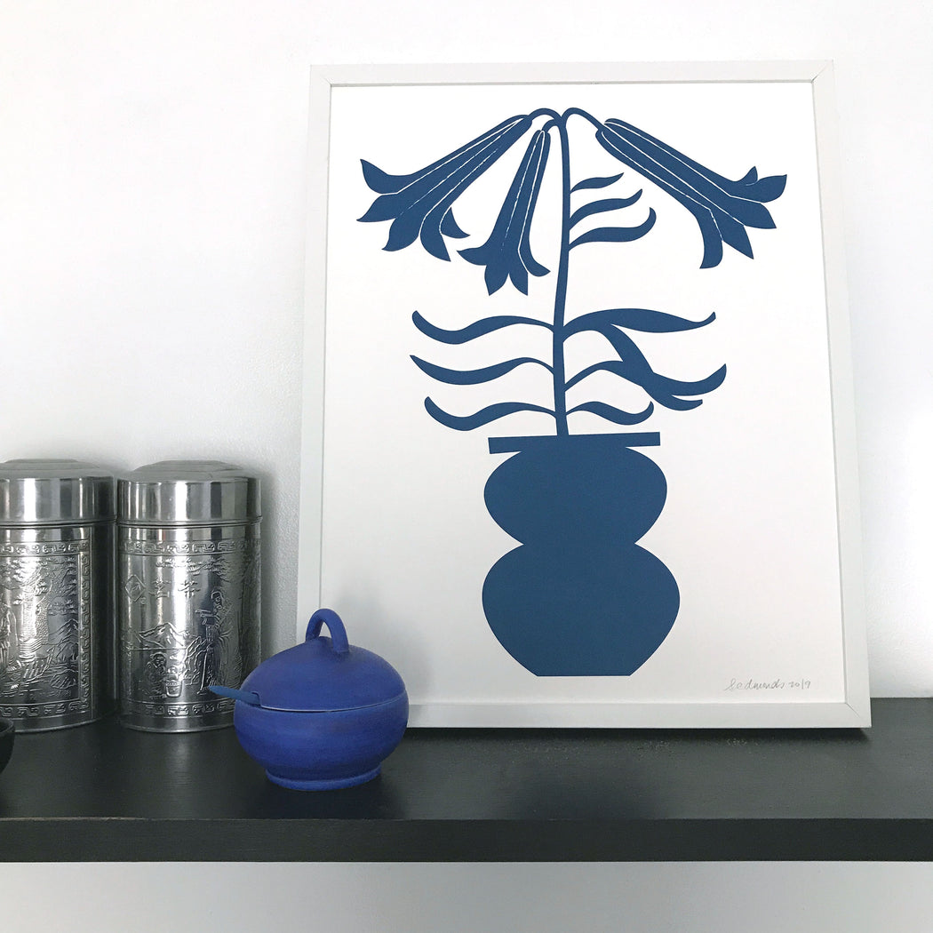 Framed print of a blue blooming lily stem in a vase