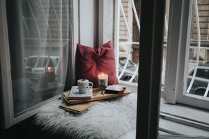 A reading nook by a window set up with a red pillow, a warm drink, a candle and some books.