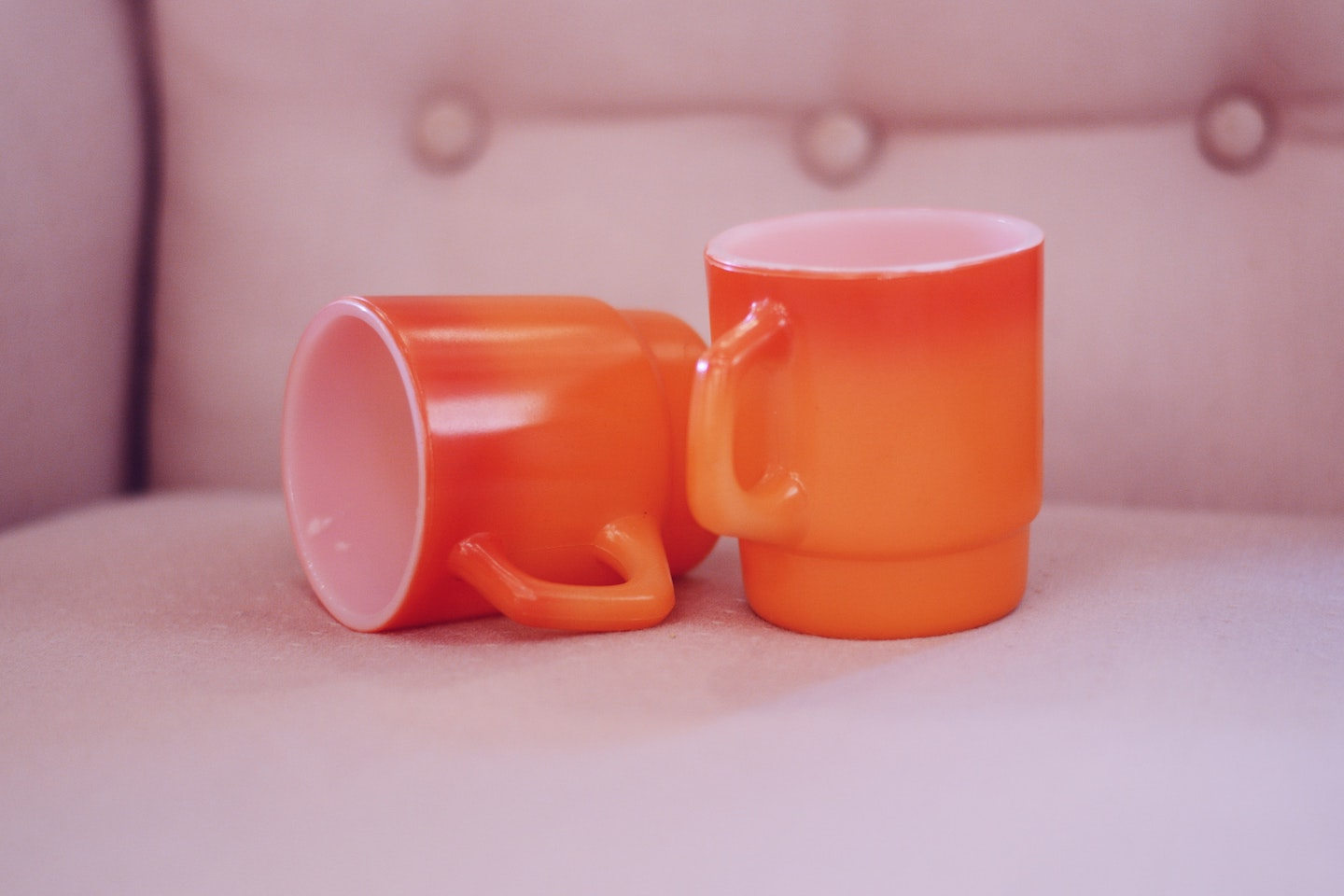 Two empty orange mugs are seen on a chair. One is laying sideways.