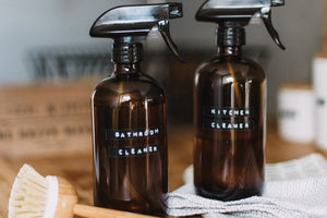 "Two homemade cleaners in amber-glass spray bottles sit on a wooden counter. One of the bottles is labeled ""Bathroom Cleaner"", the other is labeled ""Kitchen Cleaner"". There is a wooden dish brush laying nearby."