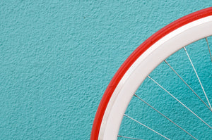 A White bicycle wheel with a red tire against a blue wall.