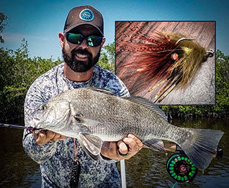Capt. Jonathan Moss with a fly caught black drum and the fly that got it done.