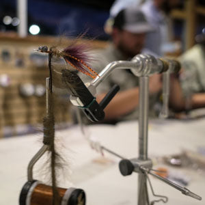 Vise with partially tied fly.