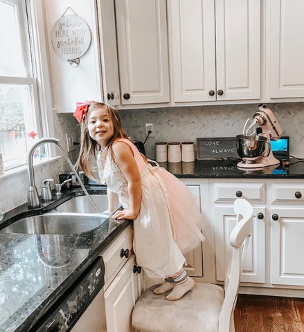 child in farmhouse kitchen wearing apron baking cookies with mom