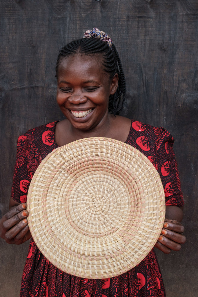 Artisan Christine shows one of her woven baskets