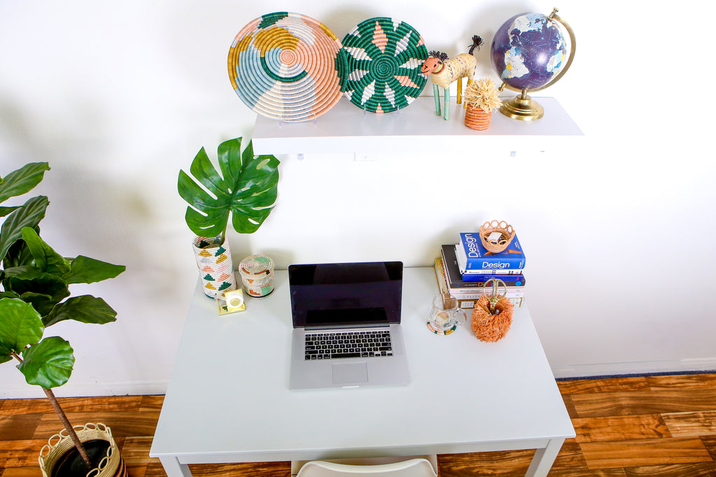 Home office desk and shelves showing art, organizer boxes and computer