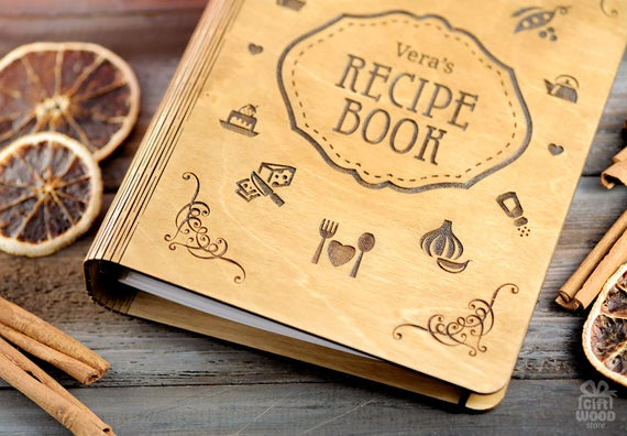 Wooden engraved cover of a personalized cookbook laying on table