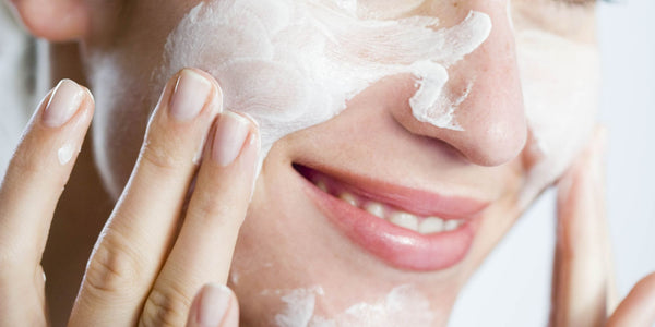 Woman rubbing lotion on her face and smiling