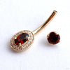Oval Halo Curved Barbell in Gold with Garnet & Clear CZ from BVLA