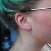 Triple earlobe piercing with Bezel-set Cabochon Press-fit End in Titanium from NeoMetal in White Coral