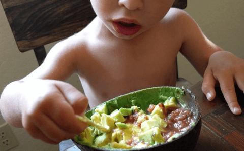 toddler eating avocado