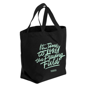 "All black canvas tote with the words ""It's time to level the playing field"" in Liberty Green font."