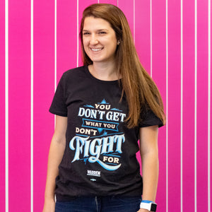 "A Warren for President staff member in a black ""You Don't Get What You Don't Fight For"" t-shirt. (4042812293229)"