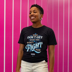 "A Warren for President staff member in a black ""You Don't Get What You Don't Fight For"" t-shirt."