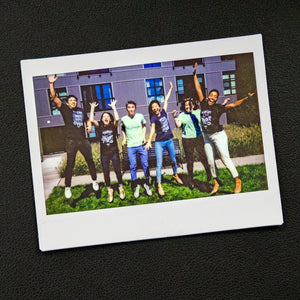 A Polaroid photo of Warren staff jumping outside.