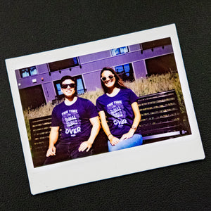 "A Polaroid photo of two Warren staff wearing the ""The Time For Small Ideas Is Over"" shirt."