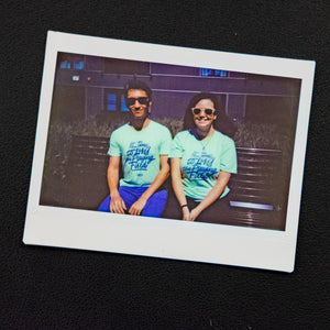 "A Polaroid photo of two Warren for President staff members wearing the liberty green ""It's Time To Level The Playing Field"" shirts."