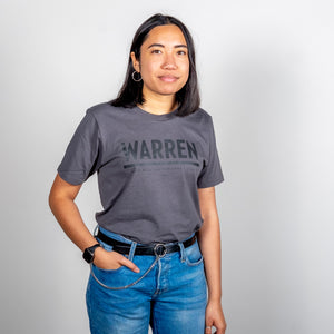 Warren Minimalist Unisex Asphalt T-shirt with Black Text on model with shirt tucked and hand in pocket.