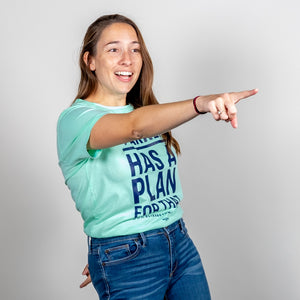 Liberty Green Warren Has A Plan For That Unisex T-Shirt tucked in on model, pointing enthusiastically.  (4052827177069)
