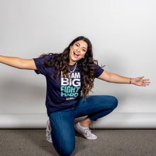 Load image into Gallery viewer, Dream Big, Fight Hard Unisex Navy T-shirt with White and Liberty Green Text. On model kneeling with open arms.