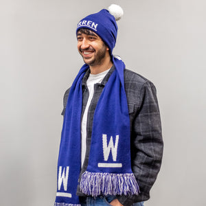 Model wearing navy knit hat with pompom and navy scarf with white Warren Ws on each end of the scarf. Navy and white fringe at the ends of the scarf.
