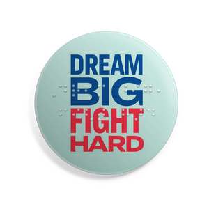"Dream Big, Fight Hard 2.5"" button with Braille overlay. Liberty green button with navy and red text.x"