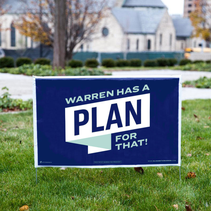 Yard sign in grass that has a navy background with the phrase