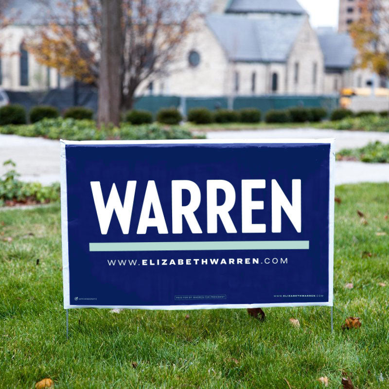 Navy yard sign with WARREN in white underlined in liberty green with www.elizabethwarren.com in white beneath the line.