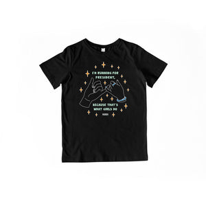 "Youth-sized black T-Shirt with pinky promise hands and the words ""I'm running for president, because that's what girls do"" in liberty green lettering."