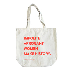 "Natural colored tote with the words ""impolite arrogant women make history."" stacked in red."