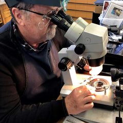 Jeweler inspecting a piece of jewelry in a microscope