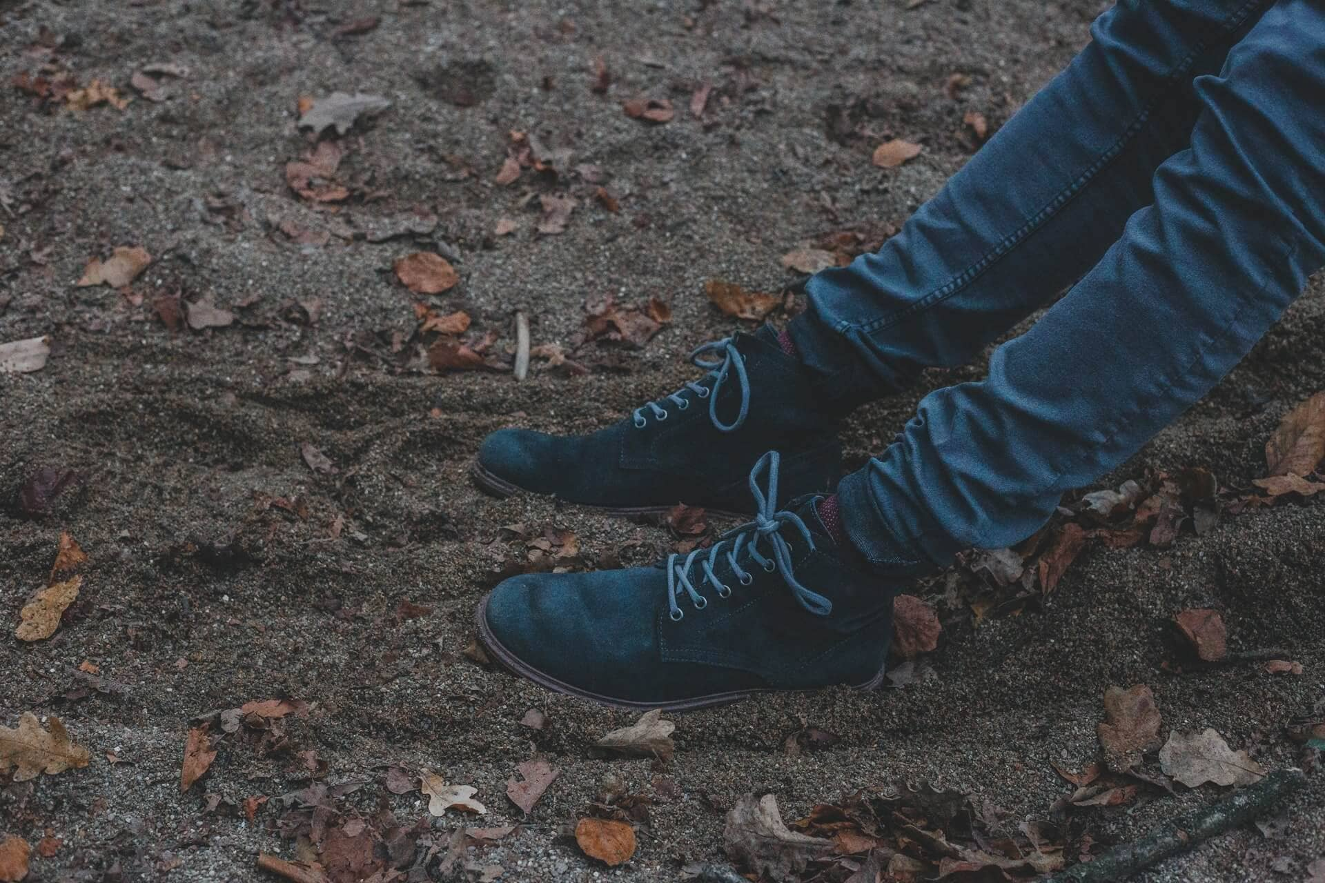 A man's legs wearing jeans and boots