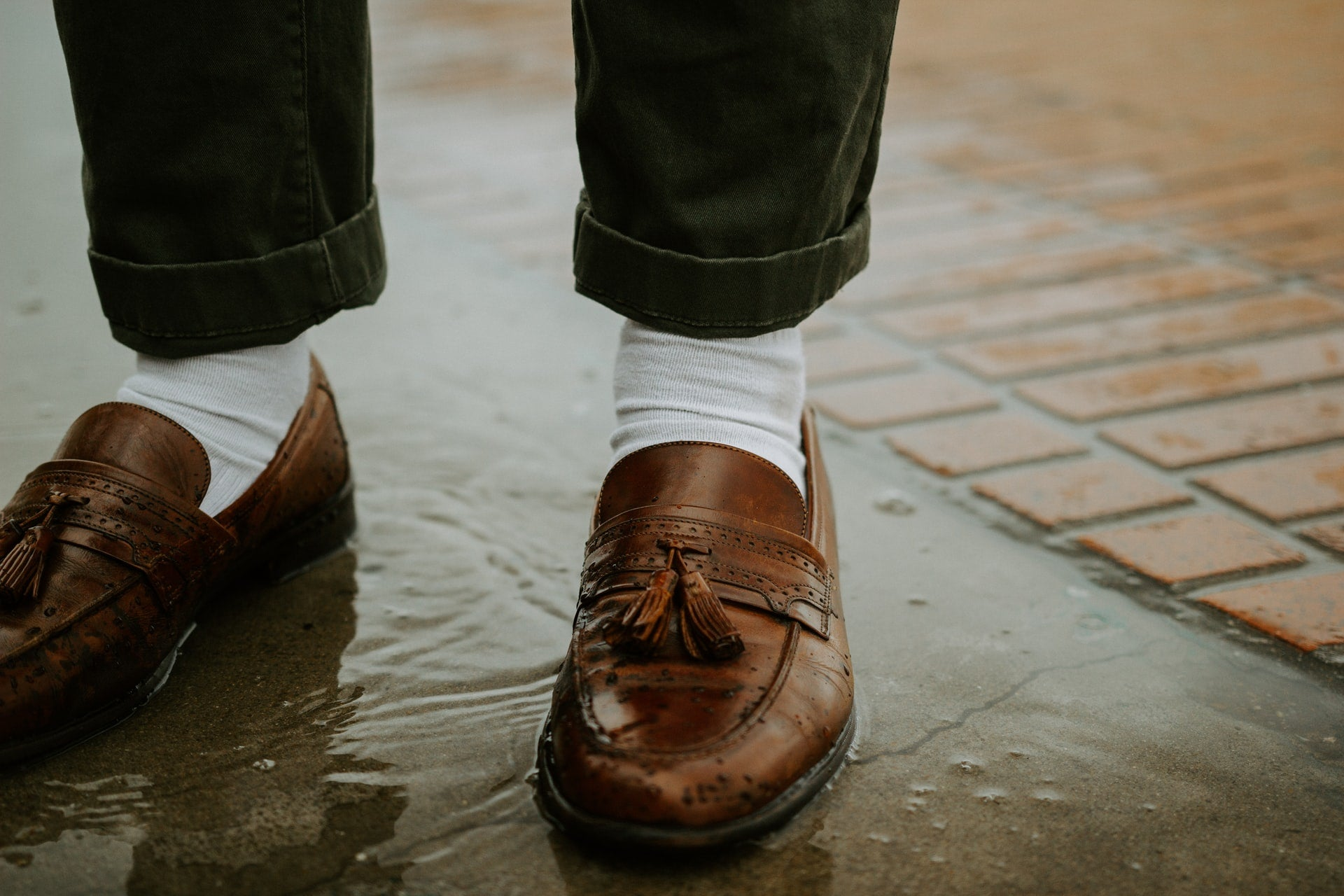 A close-up of brown tassel loafers
