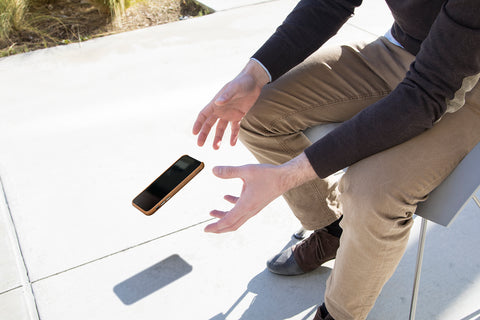 Man Dropping Leather Phone Case With Drop Protection