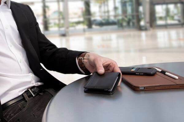 Man sitting with a wallet, cellphone, and iPad on a table