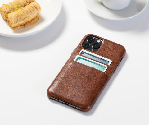 brown leather cell phone case next to white plate