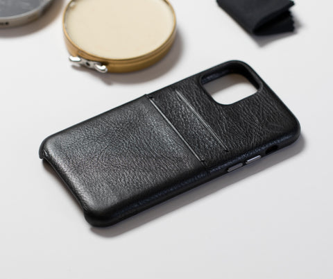black leather cell phone case on white table