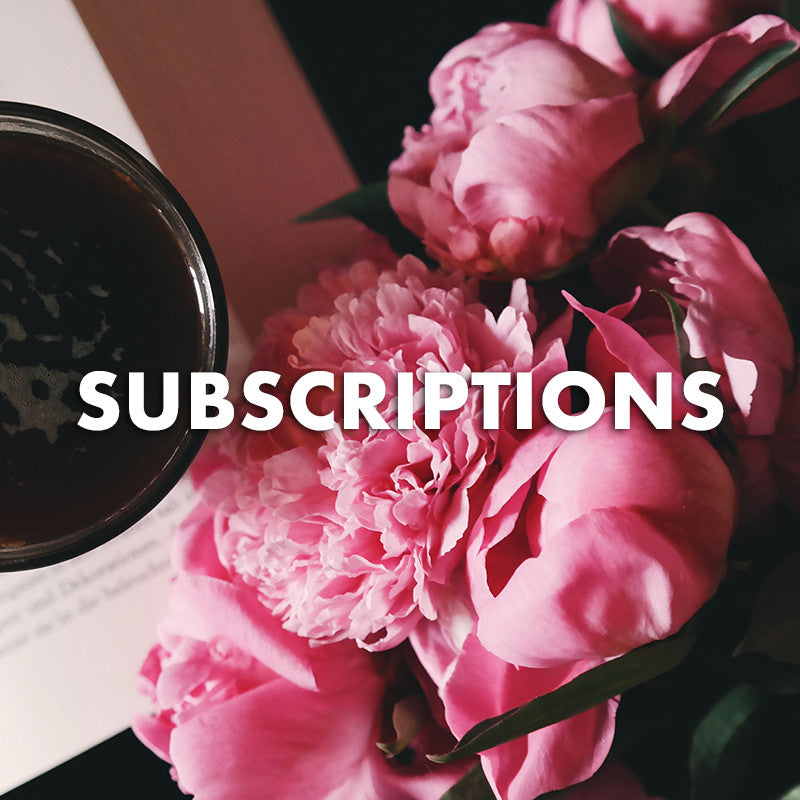 A subscription with a bouquet of pink peonies on a pad of paper with a cup of coffee