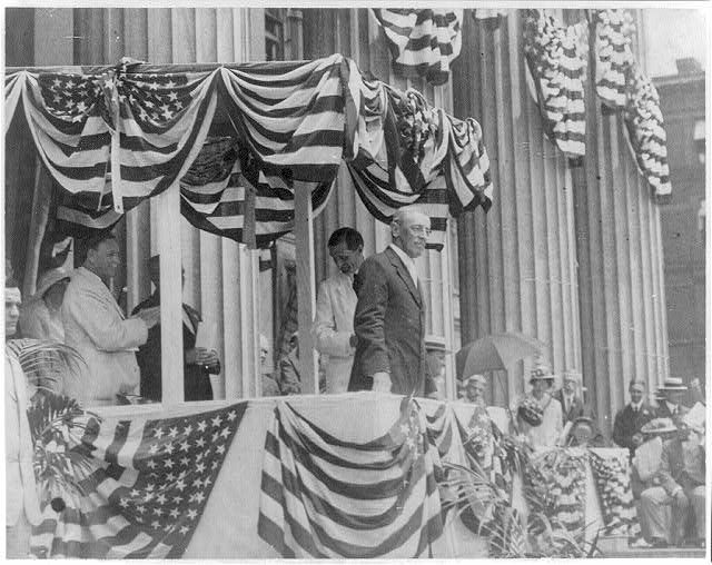 8 x 10 Reprinted Old Photo of [Woodrow Wilson, 1856-1924, half-length, facing right, standing on flag-bedecked podium on Flag Day, May 1915] 1921 National Photo Co  76a