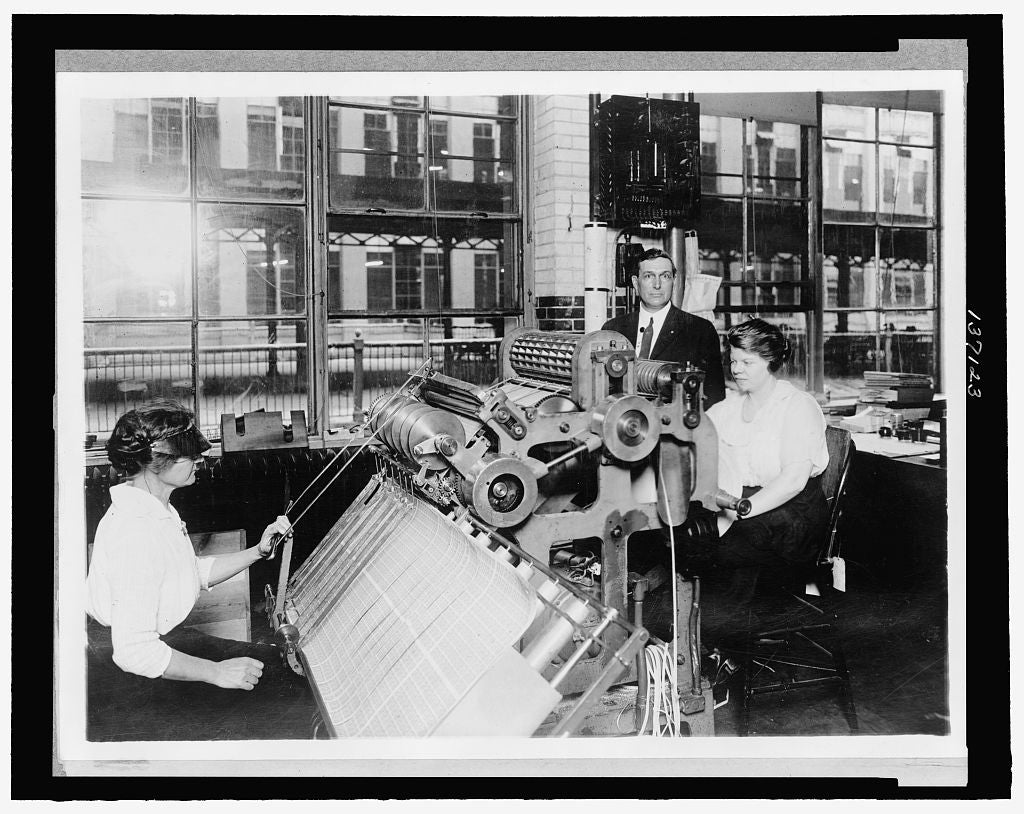 8 x 10 Reprinted Old Photo of Photograph shows a woman seated at a perforating machine with Benjamin R. Stickney, the machine's designer, standing alongside. 1921 National Photo Co  01a