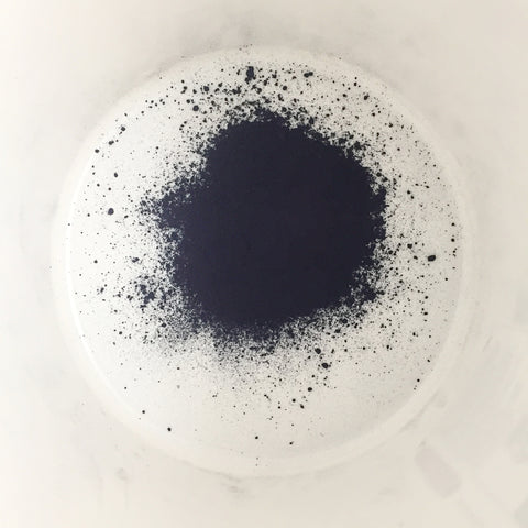 natural organic indigo powder in a bucket is so dark it looks almost black