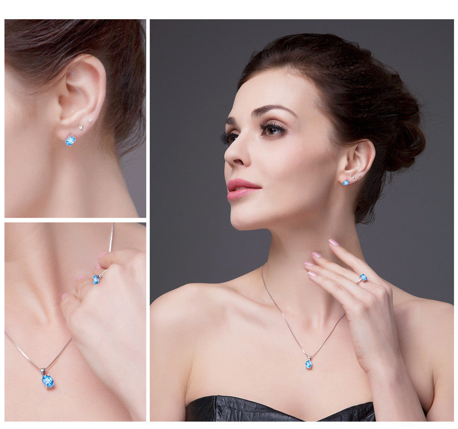 woman wearing blue topaz necklace earring and ring set