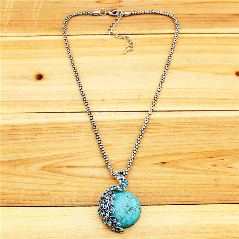 `turquoise colored peacock pendant with natural stone and rhinestones